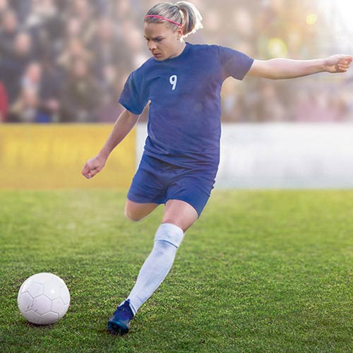 Eugenie Le Sommer kicking a football on the field.